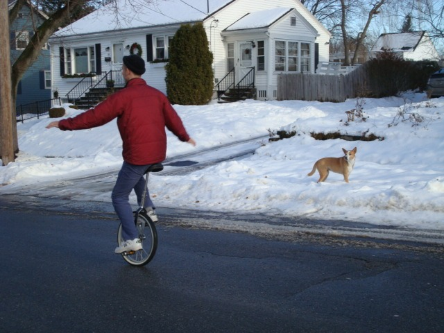 neil sattin rides a unicycle in winter while nola looks on amazed