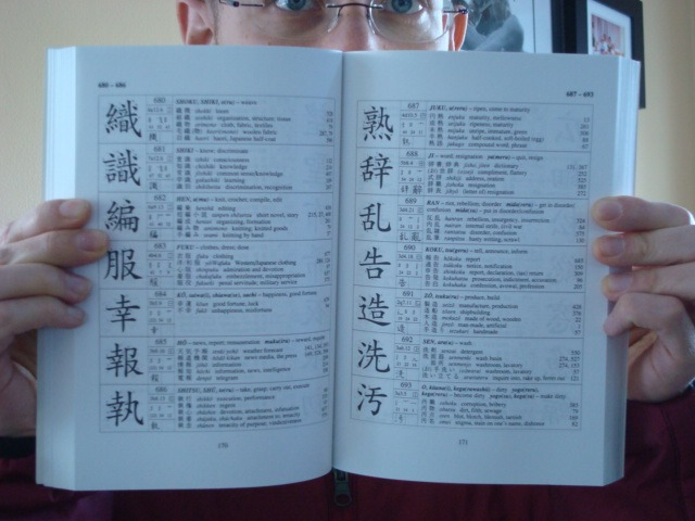 neil opens a page of the kanji book